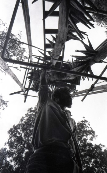 Photograph of Raghav Kaneria in Front of a Wooden Installation