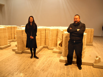 Artist couple Ai Weiwei and Lu Qing standing in front of Ai's work, World Map