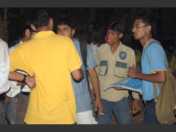 Shocked students and faculty gather at night to plan action.