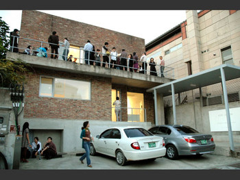 The crowd at Kim Jiwon's opening gathers at the balcony of the PKM Gallery.
