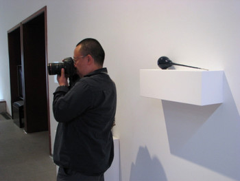 Installation View.Sculptor Cao Hui taking photos at the exhibition.