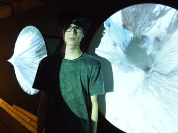 Taiwanese artist Weng Wei-Hsiang in front of his work Space as a Limit, 2008, video projection on stretched fabric