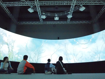 Viewers sitting in Tim Gruchy's installation CU: Clesthyra's Undoing, 2009, interactive, 360 degree multimedia, 350x1400x400cm