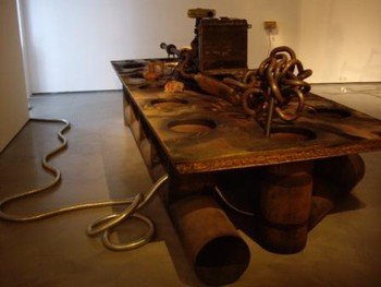 Riyas Komu, Ballad of the Distracted vs. Cult of the Dead of the Memory Loss, Recycled wood, metal, Fiat taxi engine, automotive paint, car battery, plastic, fuel, rubber, sack and electric wire, 2009, at 'THE DARK SCIENCE of Five Continents', Gallery BMB