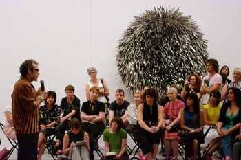 Artist talk by Subodh Gupta; (background) The other thing, 2005-06, steel structure, plastic, stainless steel tongs