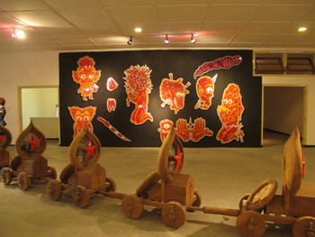 Installation view, Front: Riyas Komu, Undertakers III, 2008, wood, automotive paint, archival prints on linen and copper, 120 x 105 x 61 cm;<br/> Back: Wedhar Riyadi, Holy War #1 and #2, 2011, painted aluminum, dimensions variable