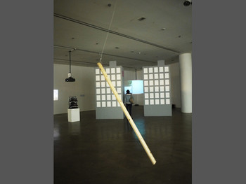 Front, Alicia Frankovich, Choreograph 1, 2011, wood, engineered mechanism, steel, dimensions variable; back, Jun Yang, Seoul<br/> Fiction, 2010, super 16mm film transferred to HD video, color, stereo sound, 15 min