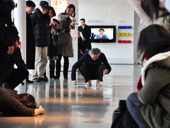Kunyong Lee, reenacting his Snail's Gallop performance at the 'Above all' opening. He squatted down and drew a chalk line, at the same time erasing his traces with his feet. Photo courtesy: Gyeonggi MoMA