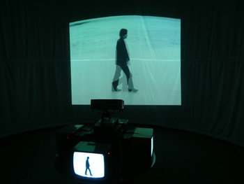 Taejin Yook, Walking Man, 1996, projector, monitor, motor, DVD  During the 1980s and 1990s, Taejin Yook (1961-2008) produced video and kinetic works with a focus on popular culture in urban space and the individuals who occupy this space. In Yook's art, not only do the human figures featured in the videos move, but so do the mechanical devices with which the video is projected, doubly ensuring a kinetic viewing experience.
