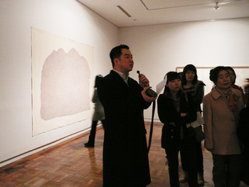 Jinsang Yoo, curator of the 'Abstract It' exhibition, explains the artworks for the public