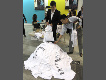 "Gallerists distributing t-shirts imprinted with 'Where is Ai Wei Wei?"" to visitors"