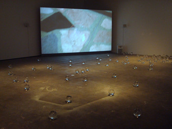 Rivane Neuenschwander, The Tenant, 2010, video.  Ryan Gander, A sheet of paper on which I was about to draw, as it slipped from my table and fell to the floor, 2008, installation.  Presented at the Yokohama Museum of Art