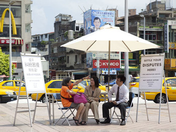 Carey Young, Conflict Management (installation view, Taipei, 2010), 2003. Professional arbitrator (dispute resolution specialist) sited<br/> in a marketplace for the period of one day, table, three chairs, two notice boards, local media advertising, members of the public.<br/> Courtesy of TFAM.