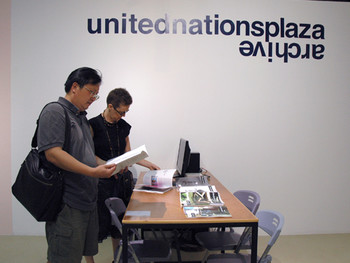 Visitors reading copies of e-flux journals at the corner entitled 'unitednationsplaza archive'