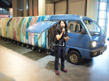 Artist Yin Xiuzhen (尹秀珍) talking to the press in front of her work Collective Sub-consciousness, 2007, minibus, stainless steel, used clothing, stools, music, 140 x 190 x 1220/1420 cm