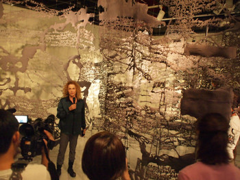 Artist Penny Hes Yassour talking to the press, standing in front of her work I am Writing You Tomorrow, 2008, mixed media, dimensions variable