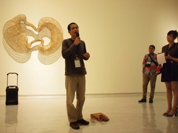 Artist Sopheap Pich presenting his work to the press, on the wall behind is his 2008 piece Cycle 2, rattan, wire, 203 x 135 x 30 cm