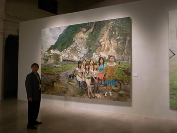 A spectator standing before Liu Xiaodong's Getting Out of Beichuan, 2010, oil painting.