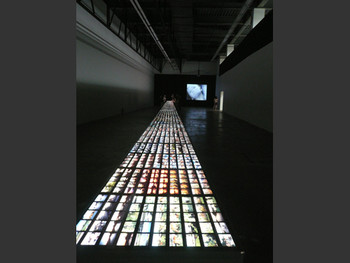 Installation view, Peter Fischli/David Weiss, Visible World, 1986-2001, light table with 3,000 photographs; (back) Peter Roehr,<br/> Film-Montagen I-III, 1965, 21 short black-and-white films transferred to DVD, 22:53.