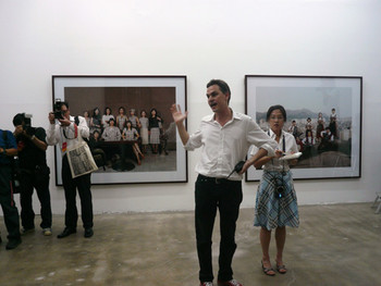 Artistic Director Massimiliano Gioni giving a speech in front of Sanggil Kim's artworks; (left) off‐line_burberry internet community,<br/> 2004, c-print; (right) off‐line_the sound of music internet community, 2005, c-print