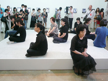 Sanja Iveković, On the Barricades, 2010, digital photographs and performance. This is a living memorial to commemorate the victims<br/> of the Gwangju People's Uprising of May 18, 1980, and is enacted by volunteers who stand in place of statues representing the<br/> victims, humming a song that was a marching anthem during the uprising.