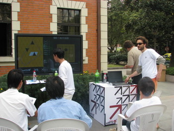 Organizers of Augmented Go watching the progress of the game in front of a TV screen.