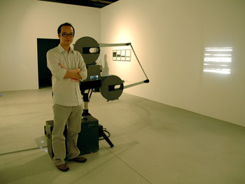 Tozer Pak and his 35 mm film-projecting machine for his installation