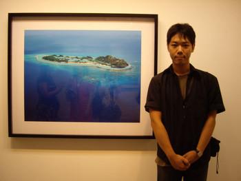 Ryuro Fukuda in front of his photography, Infinite Islands, 2003-2007.