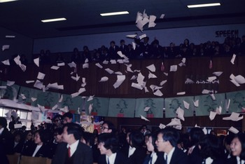 Image: Students threw out pieces of paper in beige and white colour from the upper circle of the school hall. Action led by Frog King. Kwok Mangho Frog King Archive, Asia Art Archive.