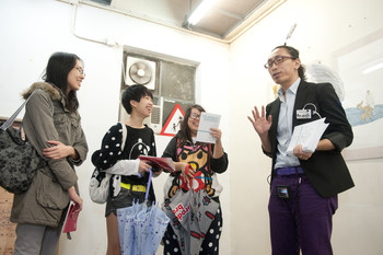 Image: Audience members interacting with Jeff at his mobile show <i> Wearable Exhibition: Bring Art Everywhere</i> (2011), during which Jeff walked around different studios in Fo Tan while wearing various artworks.