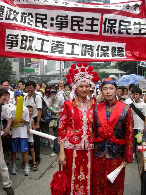Image: Engagement of artists Clara Cheung and Gum Cheng (C&G) in traditional wedding outfits during the rally on Handover Day in 2014. Courtesy of C&G.